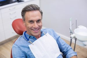 man in dentist chair smiling after receiving his new dental crown